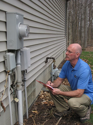 Home Inspector Examining Exterior Meters on Home