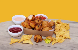 Multiple types of snacks in a box served with nachos and three dips