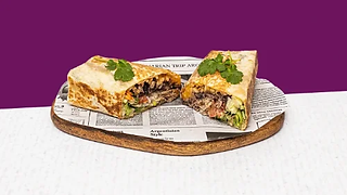 Pork burrito cut in half served on a wooden plate