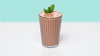 Glass of chocolate milkshake with mint