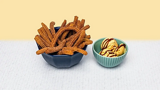 Churros in a bowl with vanilla ice cream