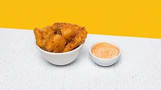 Bowl of home-made chicken nuggets with a mayonnaise sauce