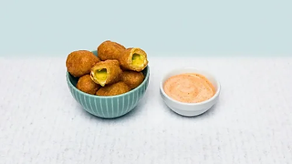 Bowl of fried jalapeno croquettes with cheese and mayonnaise sauce