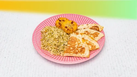 Kids quesadilla with lime rice and corn cob served on a pink plate