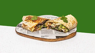 Vegetarian burrito cut in half served on a wooden plate