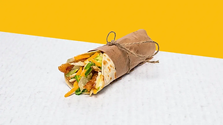 Small wrap with home-made chicken nuggets wrapped in paper
