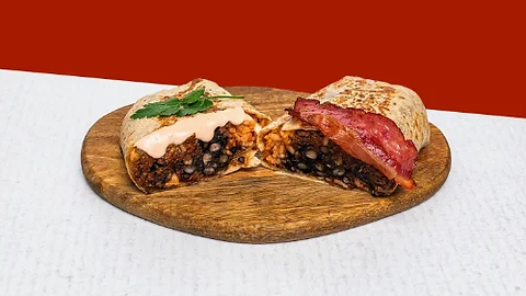 Burrito with minced beef and bacon served on a wooden plate