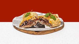 Beef burrito cut in half served on a wooden plate