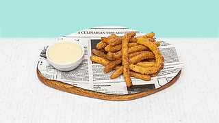 Churros with chcolate dip served on a wooden plate