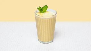 Glass of vanilla milkshake with mint