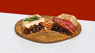 Burrito with ground beef and bacon cut in half served of a wooden plate.