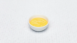 Small bowl of yellow cheese sauce
