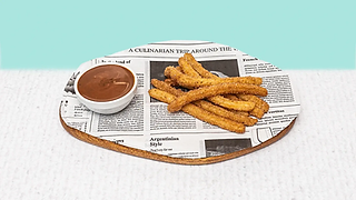 Churros served on a wooden plate with chocolate dip