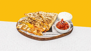 Chicken quesadilla served on a wooden plate with sour cream and salsa