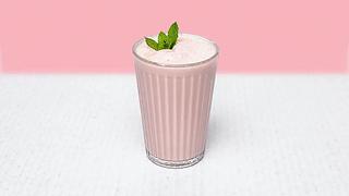 Glass of strawberry milkshake with mint