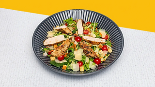 Caesar salat with grilled chicken breasts served on a large plate.