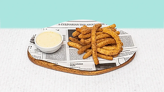 Churros served on a wooden plate with white chocolate dip