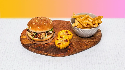 Small burger with french fries and corn cob served on a wooden plate