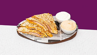 Bacon quesadilla served on a wooden plate with sour cream and salsa