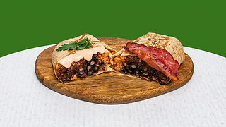 Burrito with vegan meat cut in half served of a wooden plate.