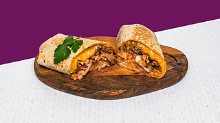Burrito with pulled pork and coleslaw cut in half served of a wooden plate.
