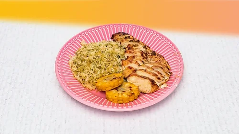 Grilled chicken breast with lime rice and corn cob served on a pink plate