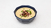 Bowl of corn soup with fried bacon