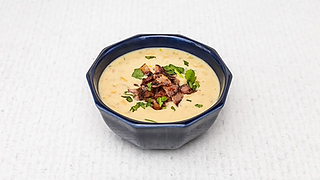 Corn soup with fried bacon served in a bloue bowl