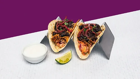 Tacos with pulled pork and coleslaw served on a steel holder