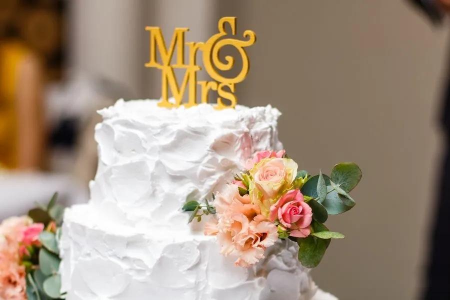 Weiße Hochzeitstorte auf silbernem Sockel mit rosa Blüten an den Seiten