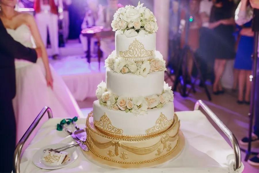 Hochzeitstorte mit weißen Rosen ein paar Sekunden vor dem anschnitt