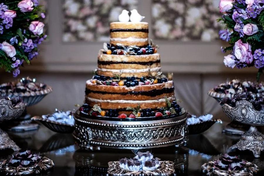Hervorragende Hochzeitstorte auf dem Tisch zwischen duftenden Blumensträußen