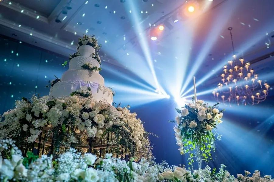 Hochzeitstorte auf der Bühne für die Hochzeitsfeier und große Discokugel mit Beleuchtung