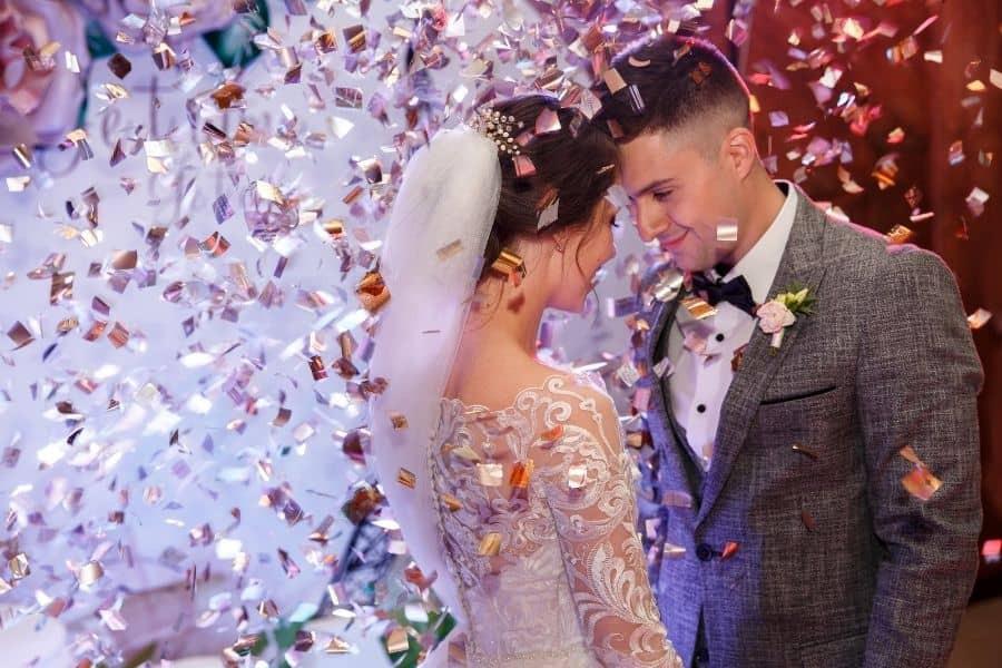 Glückliche Braut und Bräutigam tanzen unter Konfetti am Hochzeitsempfang. Hochzeit eines schönen kaukasischen Paares, Hochzeitstanz mit Spezialeffekten