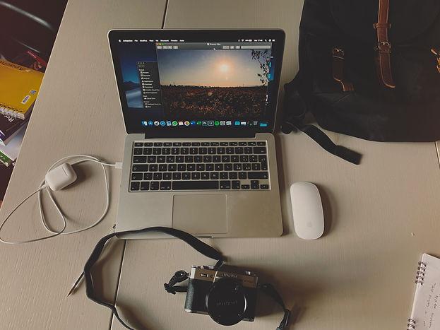 Scrivania con Macbook e macchina fotografica