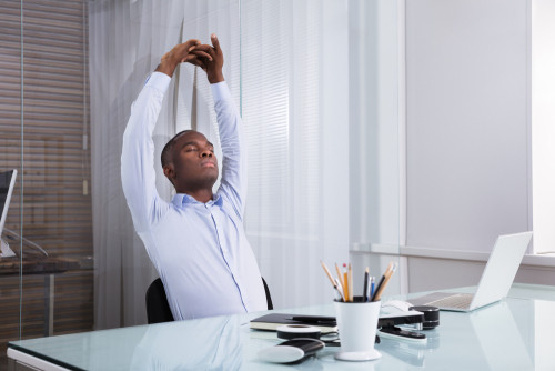 man sitting at desk stretching
