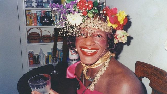 Marsha P. Johnson holding a glass and smiling