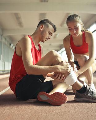woman-helping-sportsman-with-injury-duri