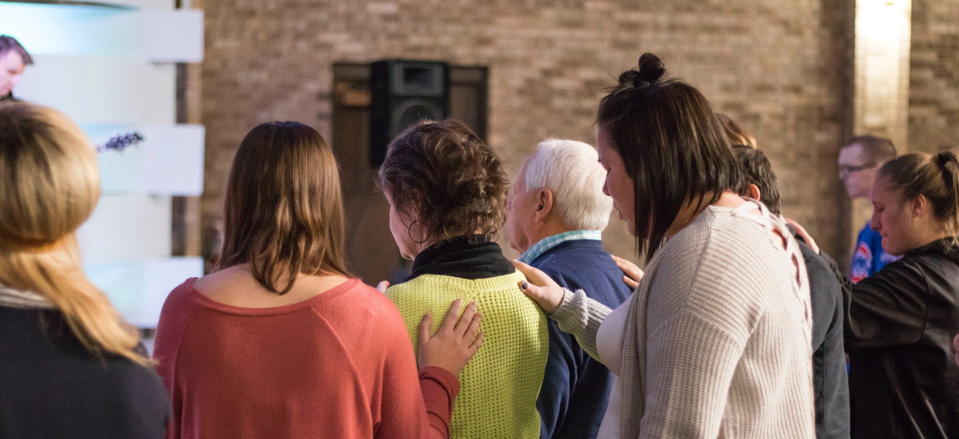 Hannah praying over someone during a worship service.
