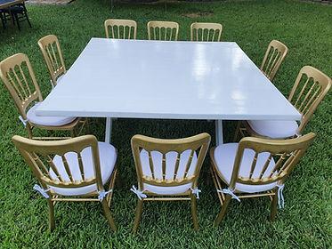 Mesa cuadrada de madera blanca con silla peineta dorada