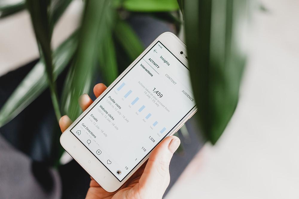 Hand hält Smartphone mit Instagram Insights Screen.
