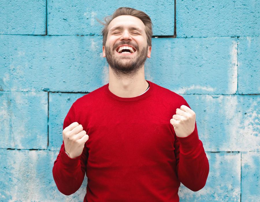 Junger Mann mit rotem Pullover | Erfolg | erfolgreich werden | Freude | Glück