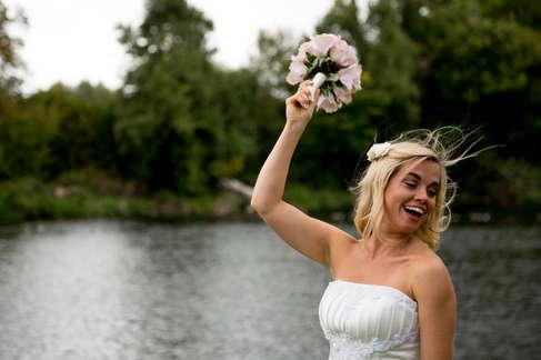 happy bride throwing wedding bouquet of flowers