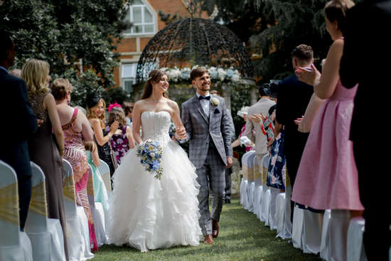 Beautiful wedding photography: Bride and groom walk down aisle at outdoor ceremony