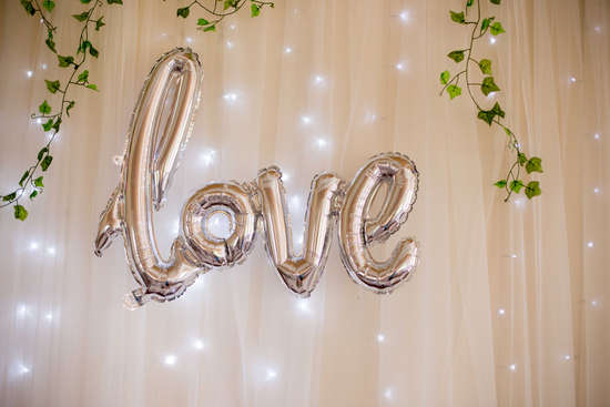 Silver love balloons and fairy light curtain