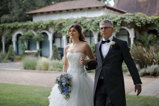 Bride walking down isle with father at outdoor wedding