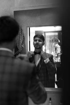 Groom getting ready in mirror during morning