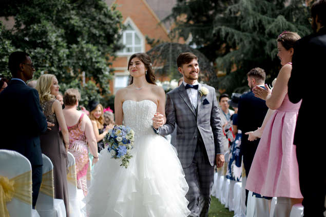 Couple walking down asile of outdoor wedding