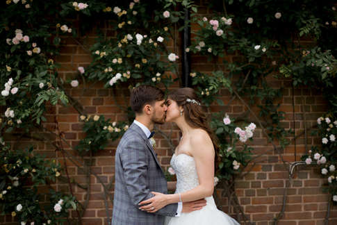 wedding photography of happy couple kissing in front of rose vines