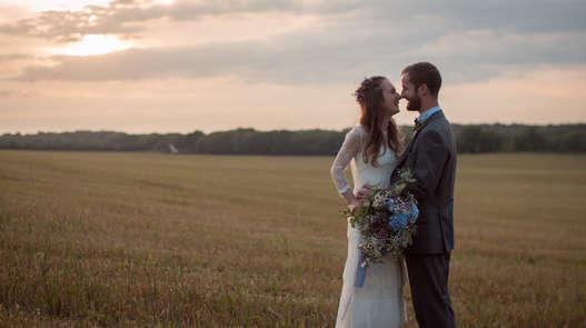 Bohemian wedding couple cuddling in corn field